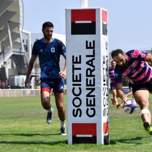 Joueur de l'association de Rugby à 7, Esprit Sud Sevens en pleine action lors d'un match, près du poteau sponsorisé par un partenaire d'Esprit Sud Sevens, Société Générale.